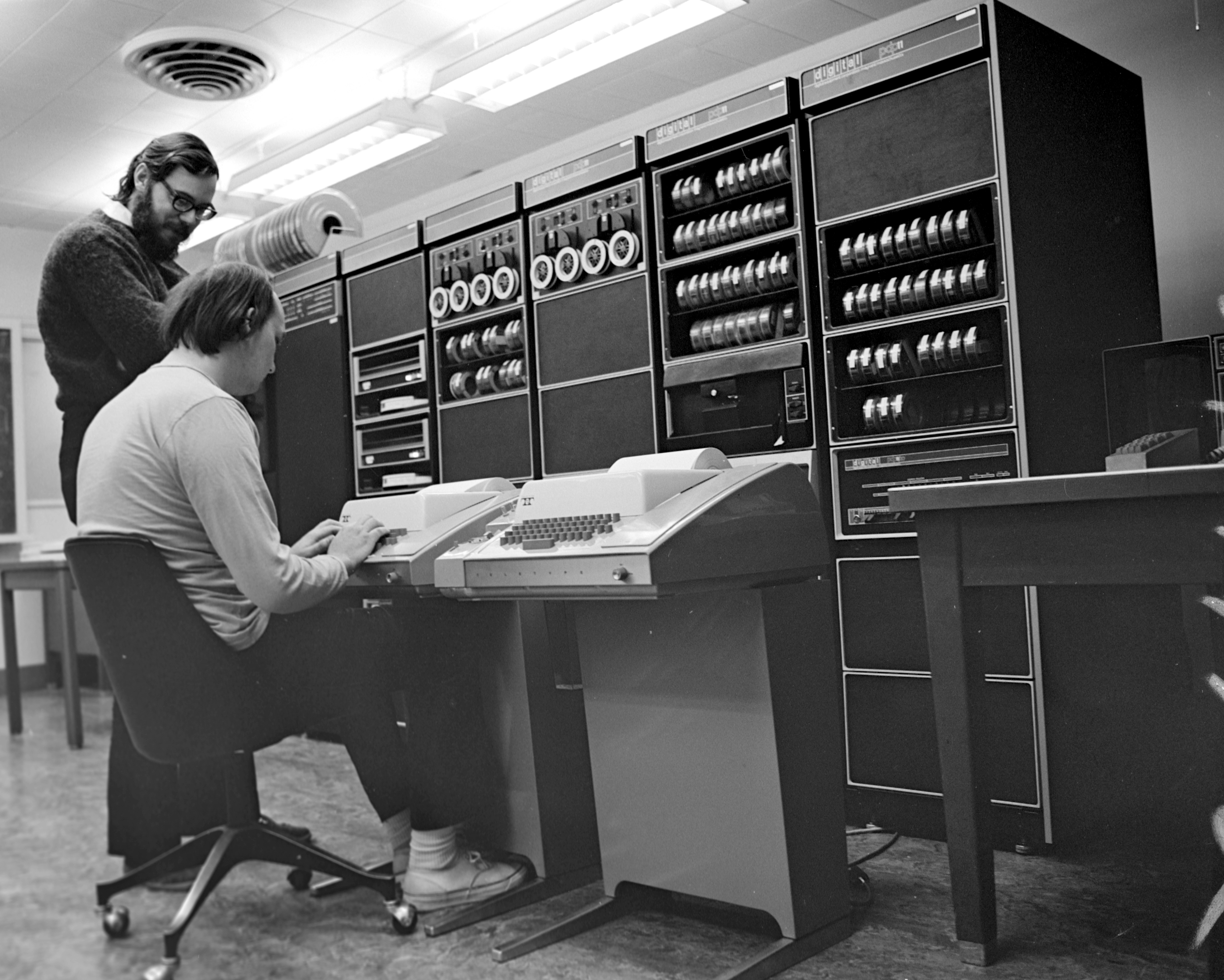 Ken_Thompson_-sitting-and_Dennis_Ritchie_at_PDP-11-2876612463-