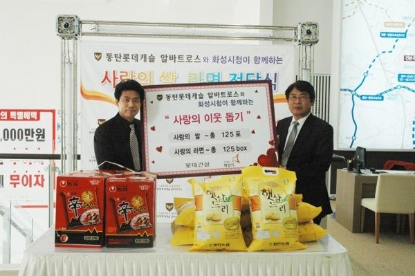 동탄롯데캐슬권소혁소장(왼쪽)이 화성시청 관계자에게 쌀과 라면을 기부하고 있다.