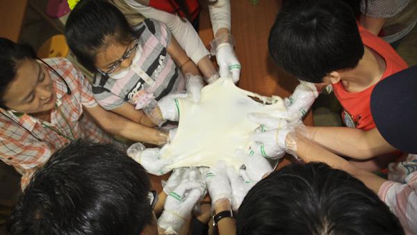 함께 만든 치즈를 늘리며 기뻐하는 아이들과 봉사단