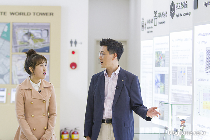롯데월드타워 홍보관을 둘러보고 있는 두 사람
