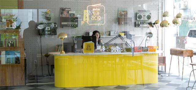 28일 서울 마포구 합정동에 마련된 동서식품의 다섯 번째 팝업 카페 '모카라디오'의 라디오 부스에서 DJ가 시민들이 적은 사연과 신청곡을 소개하고 있다. 동서식품 제공